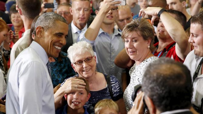 Young boys pose for a photo with U.S. President Barack Obama as Obama greets his audience after speaking about the economy during a visit to the University of Wisconsin La Crosse July 2, 2015. REUTERS/Kevin Lamarque