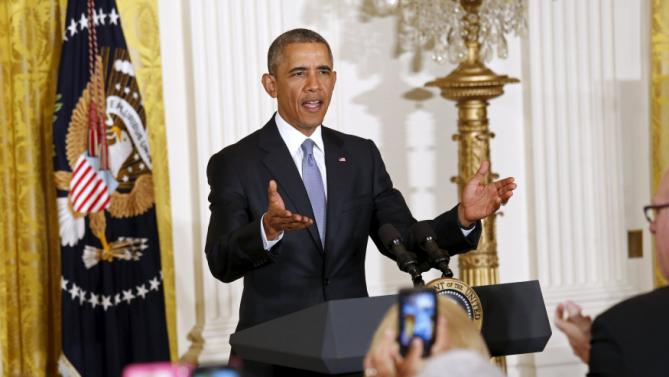 U.S. President Barack Obama gestures for guests to take their seats upon his arrival to speak during the 2015 White House Conference on Aging (WHCOA) at the White House in Washington July 13, 2015. REUTERS/Kevin Lamarque