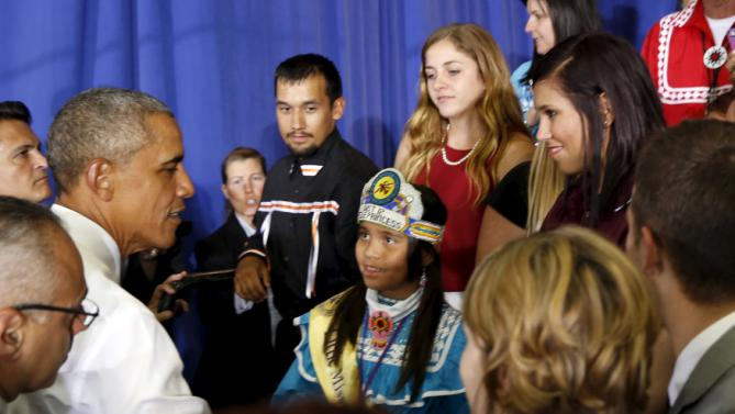 A young Choctaw girl listens and looks up at U.S. President Barack Obama as he shakes hands after speaking on expanding economic opportunity for communities across the country during a visit with the Choctaw Nation in Durant, Oklahoma July 15, 2015.  The Choctaw Nation is the country's third-largest Native American tribe. REUTERS/Kevin Lamarque