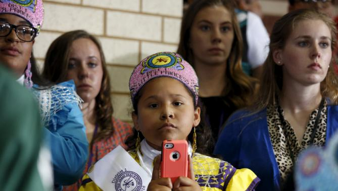 A Choctaw girl waits to take a photo as U.S. President Barack Obama works a rope line after speaking on expanding economic opportunity for communities across the country during a visit with the Choctaw Nation in Durant, Oklahoma, July 15, 2015. The Choctaw Nation is the country's third-largest Native American tribe. REUTERS/Kevin Lamarque