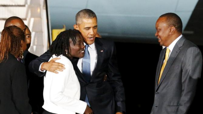 U.S. President Barack Obama (2nd L) embraces his half-sister Auma Obama (L) and is greeted by Kenya's President Uhuru Kenyatta (R) as he arrives aboard Air Force One at Jomo Kenyatta International Airport in Nairobi July 24, 2015. U.S. President Barack Obama flew into Kenya late on Friday for his first presidential visit to his father's homeland, aiming to boost trade and security ties in east Africa. Obama's Air Force One plane landed in the evening in the Kenyan capital, Nairobi, where he will co-host a conference on boosting entrepreneurs on the African continent before travelling on to Ethiopia.  REUTERS/Jonathan Ernst      TPX IMAGES OF THE DAY