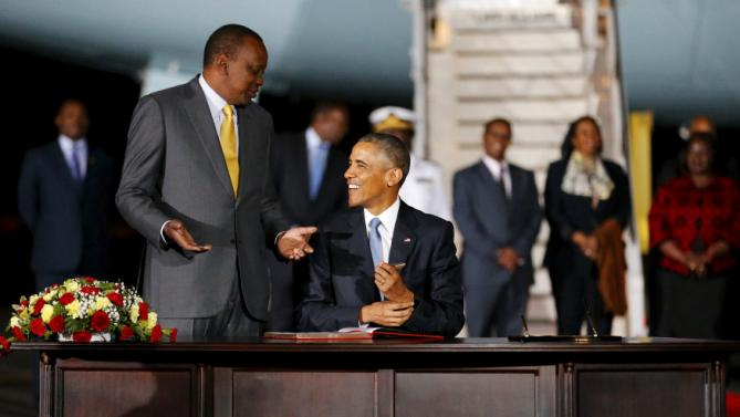 Kenya's President Uhuru Kenyatta (L) looks on as U.S. President Barack Obama signs a guest book as he arrives aboard Air Force One at Jomo Kenyatta International Airport in Nairobi July 24, 2015. U.S. President Barack Obama flew into Kenya late on Friday for his first presidential visit to his father's homeland, aiming to boost trade and security ties in east Africa. Obama's Air Force One plane landed in the evening in the Kenyan capital, Nairobi, where he will co-host a conference on boosting entrepreneurs on the African continent before travelling on to Ethiopia. REUTERS/Jonathan Ernst      TPX IMAGES OF THE DAY