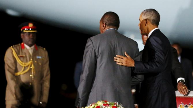 U.S. President Barack Obama (R) walks with Kenya's President Uhuru Kenyatta (C) after signing a guest book upon arriving aboard Air Force One at Jomo Kenyatta International Airport in Nairobi July 24, 2015. U.S. President Barack Obama flew into Kenya late on Friday for his first presidential visit to his father's homeland, aiming to boost trade and security ties. REUTERS/Jonathan Ernst