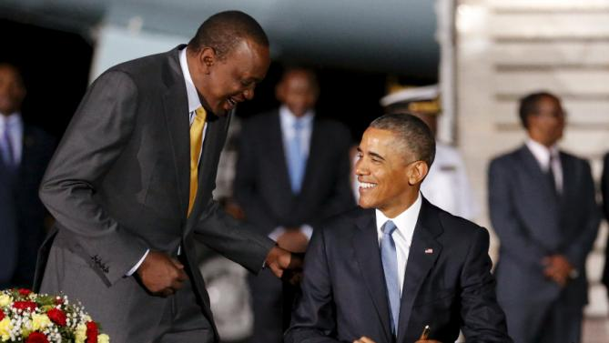Kenya's President Uhuru Kenyatta (L) looks on as U.S. President Barack Obama signs a guest book after arriving aboard Air Force One at Jomo Kenyatta International Airport in Nairobi July 24, 2015. U.S. President Barack Obama flew into Kenya late on Friday for his first presidential visit to his father's homeland, aiming to boost trade and security ties in east Africa. REUTERS/Jonathan Ernst