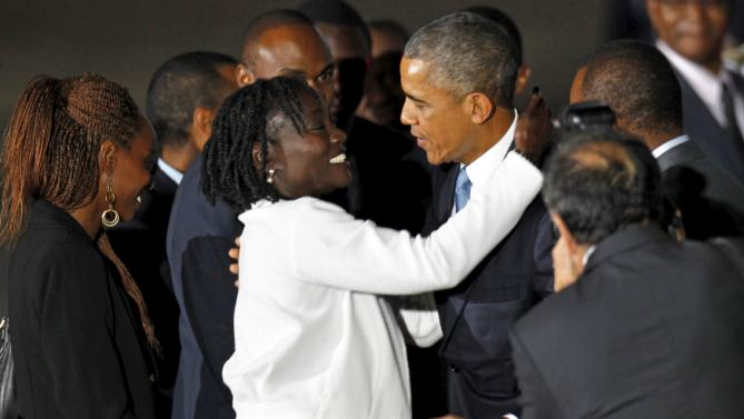 U.S. President Barack Obama (2nd R) embraces his half-sister Auma Obama (in white coat) as he arrives aboard Air Force One at Jomo Kenyatta International Airport in Nairobi July 24, 2015. U.S. President Barack Obama flew into Kenya late on Friday for his first presidential visit to his father's homeland, aiming to boost trade and security ties in east Africa. REUTERS/Thomas Mukoya