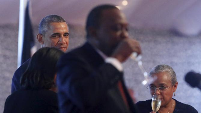 U.S. President Barack Obama (L) looks on as Kenya's President Uhuru Kenyatta (C) drinks a toast to him at the end of a state dinner in Obama's honor at the State House in Nairobi July 25, 2015. Also pictured is Kenyatta's wife Margaret Kenyatta. REUTERS/Jonathan Ernst