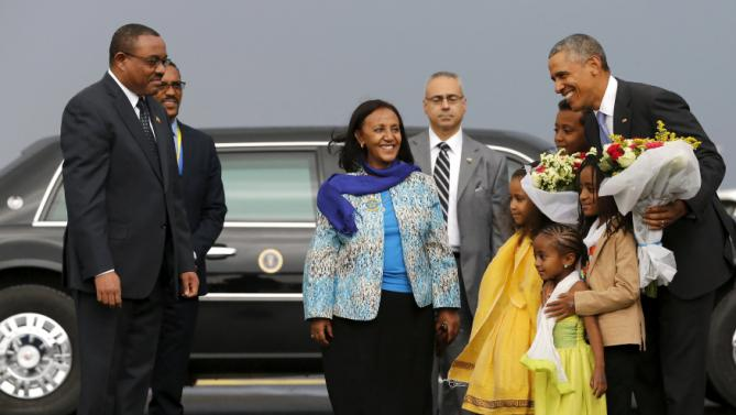 Ethiopia's Prime Minister Hailemariam Desalegn (L) looks on as U.S. President Barack Obama (R) receives flowers from children as he arrives aboard Air Force One at Bole International Airport in Addis Ababa, Ethiopia July 26, 2015. REUTERS/Jonathan Ernst