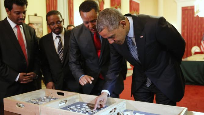 Dr. Zeresenay Alemseged Lemseged (2ndR), of the California Academy of Sciences,  directs U.S. President Barack Obama (R) to touch a fossilized vertebra of Lucy, an early human, before a State Dinner in Obama's honor at the National Palace in Addis Ababa, Ethiopia July 27, 2015. Lucy is the most famous fossil of the species Australopithecus afarensis, and was found in Ethiopia in 1974. REUTERS/Jonathan Ernst