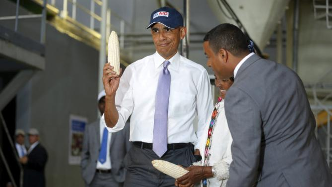 U.S. President Barack Obama (L) shows off a ear of corn grown by a farmer (2nd R) participating in the Feed the Future program as he tours the Faffa Food factory in Addis Ababa, Ethiopia July 28, 2015. Obama told Ethiopia's leaders on Monday that allowing more political freedoms would strengthen the African nation, which had already lifted millions out of a poverty once rooted in recurring famine. REUTERS/Jonathan Ernst
