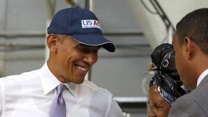 U.S. President Barack Obama (L) speaks with a farmer (2nd R) participating in the Feed the Future program as he tours the Faffa Food factory in Addis Ababa, Ethiopia July 28, 2015. Obama told Ethiopia's leaders on Monday that allowing more political freedoms would strengthen the African nation, which had already lifted millions out of a poverty once rooted in recurring famine. REUTERS/Jonathan Ernst