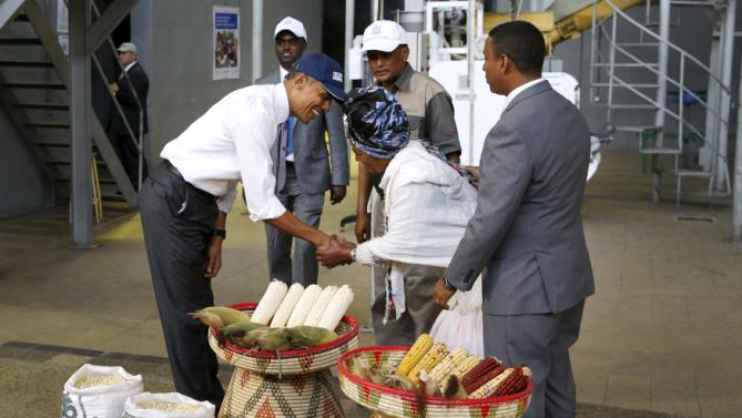 U.S. President Barack Obama (L) bows deeply as he greets a farmer (front C) participating in the Feed the Future program as he tours the Faffa Food factory in Addis Ababa, Ethiopia July 28, 2015. Obama told Ethiopia's leaders on Monday that allowing more political freedoms would strengthen the African nation, which had already lifted millions out of a poverty once rooted in recurring famine. REUTERS/Jonathan Ernst