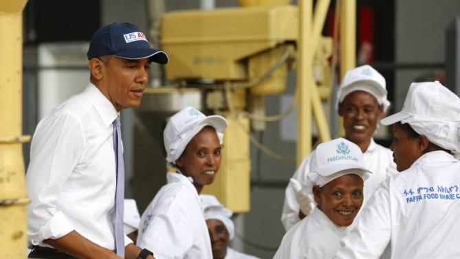 U.S. President Barack Obama (L) greets workers as he tours the Faffa Food factory in Addis Ababa, Ethiopia July 28, 2015. Obama told Ethiopia's leaders on Monday that allowing more political freedoms would strengthen the African nation, which had already lifted millions out of a poverty once rooted in recurring famine. REUTERS/Jonathan Ernst