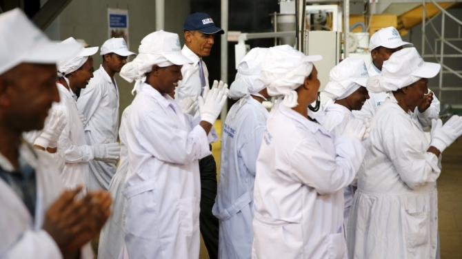 Workers applaud after greeting U.S. President Barack Obama (C) as he tours the Faffa Food factory in Addis Ababa, Ethiopia July 28, 2015. Obama told Ethiopia's leaders on Monday that allowing more political freedoms would strengthen the African nation, which had already lifted millions out of a poverty once rooted in recurring famine. REUTERS/Jonathan Ernst