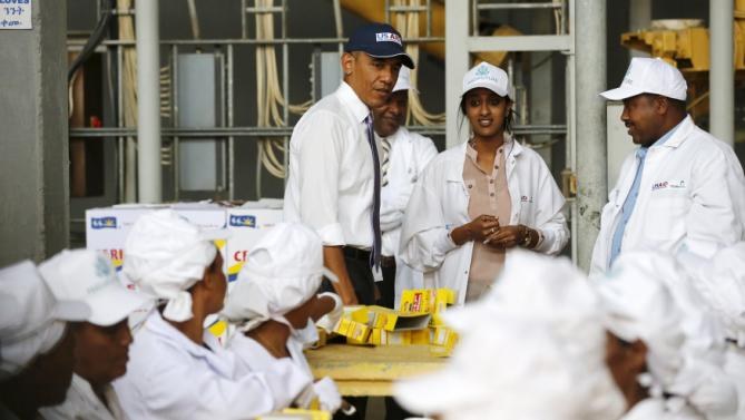 U.S. President Barack Obama (C) looks on as workers demonstrate part of the packaging process as he tours the Faffa Food factory in Addis Ababa, Ethiopia July 28, 2015. Obama told Ethiopia's leaders on Monday that allowing more political freedoms would strengthen the African nation, which had already lifted millions out of a poverty once rooted in recurring famine. REUTERS/Jonathan Ernst
