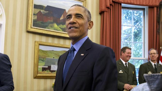 President Barack Obama, walks away from his desk after signing a designation of three new national monuments; Berryessa Snow Mountain in California, Waco Mammoth in Texas, and the Basin and Range in Nevada, in the Oval Office of the White House Friday, July 10, 2015, in Washington. (AP Photo/Jacquelyn Martin)