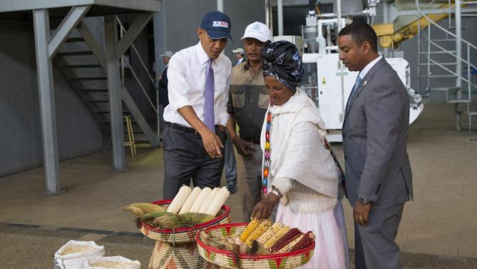 U.S. President Barack Obama, left, talks with farmer Gifty Jemal Hussein, second from right, about her corn during a tour of Faffa Food, on Tuesday, July 28, 2015, in Addis Ababa, Ethiopia. On the final day of his African trip, Obama is focusing on economic opportunities and African security. (AP Photo/Evan Vucci)