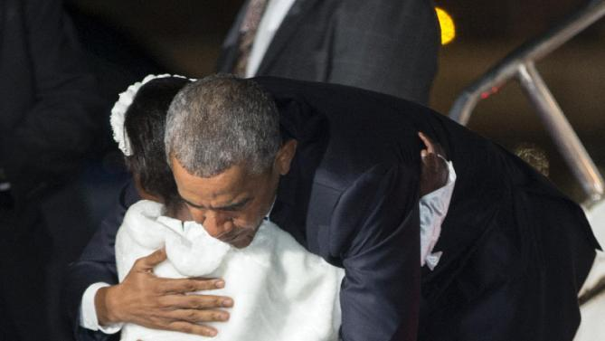 President Barack Obama hugs Joan Wamaitha, 8, who presented him with flowers, as he arrives at Kenyatta International Airport, on Friday, July 24, 2015, in Nairobi, Kenya. Obama is traveling on a two-nation African tour where he will become the the first sitting U.S. president to visit Kenya and Ethiopia. (AP Photo/Evan Vucci)