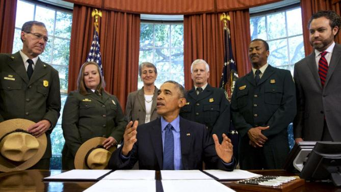 President Barack Obama, center, talks about the designation of three new national monuments; Berryessa Snow Mountain in California, Waco Mammoth in Texas, and the Basin and Range in Nevada, in the Oval Office of the White House Friday, July 10, 2015, in Washington. Behind him from left are Victor Knox, associate director of park planning, facilities and lands of the National Park Service; April Slayton, chief of public affairs and  chief spokesperson of the National Park Service; Secretary of the Interior Sally Jewell; U.S. Forest Service Chief Tom Tidwell; Randy Moore, Forest Service; and Bureau of Land Management director Neil Kornze. (AP Photo/Jacquelyn Martin)