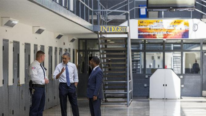 President Barack Obama speaks during a tour by Bureau of Prisons Director Charles Samuels, right, and correctional officer Ronald Warlick, Thursday, July 16, 2015, at the El Reno Federal Correctional Institution in El Reno, Okla. As part of a weeklong focus on inequities in the criminal justice system, the president will meet separately Thursday with law enforcement officials and nonviolent drug offenders who are paying their debt to society at the El Reno Federal Correctional Institution, a medium-security prison for male offenders near Oklahoma City. (AP Photo/Evan Vucci)