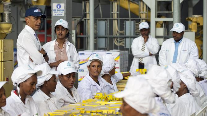 U.S. President Barack Obama watches workers package food during a tour of Faffa Food, Tuesday, July 28, 2015, in Addis Ababa, Ethiopia. On the final day of his African trip, Obama is focusing on economic opportunities and African security. (AP Photo/Evan Vucci)