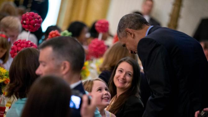 President Barack Obama greets a young guest after making an unannounced appearance as first lady Michelle Obama hosts the 2015 winners of the Healthy Lunchtime Challenge for the Kids' State Dinner in the East Room at the White House, Friday, July 10, 2015, in Washington. (AP Photo/Andrew Harnik)