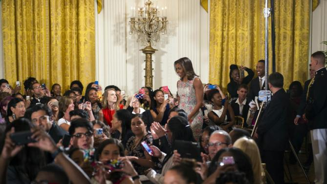 First lady Michelle Obama walks into the East Room to welcome more than 130 college-bound students from across the county to participate in the 2015 Beating the Odds Summit at the White House in Washington, Thursday, July 23, 2015. The summit is part of the first lady's Reach Higher initiative. (AP Photo/Cliff Owen)