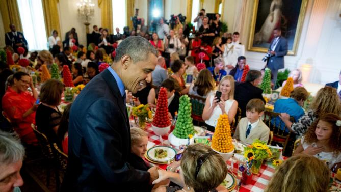 President Barack Obama greets guests after  making an unannounced appearance as first lady Michelle Obama hosts the 2015 winners of the Healthy Lunchtime Challenge for the Kids' State Dinner in the East Room at the White House, Friday, July 10, 2015, in Washington. (AP Photo/Andrew Harnik)