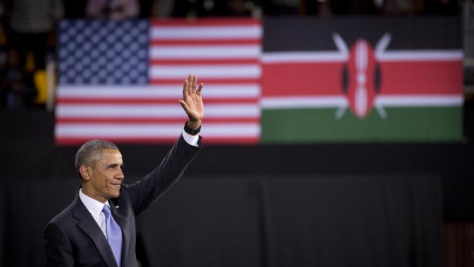 President Barack Obama waves goodbye to the crowd, underneath American and Kenyan flags, after delivering a speech at the Safaricom Indoor Arena in the Kasarani area of Nairobi, Kenya, Sunday, July 26, 2015.  Obama is traveling on a two-nation African tour where he will become the first sitting U.S. president to visit Kenya and Ethiopia. (AP Photo/Ben Curtis)
