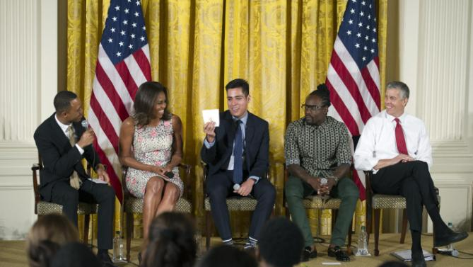 After E! News co-anchor Terrence Jenkins, left, made a joke warning guest to refrain from stealing White House napkins, Brown University student Manuel Contreras, center, holds up one of the napkins he had in his pocket as First lady Michelle Obama, Wale, center right, and Education Secretary Arnie Duncan, right, look on during an East Room event to welcome more than 130 college-bound students from across the county to participate in the 2015 Beating the Odds Summit at the White House in Washington, Thursday, July 23, 2015. The summit is part of the first lady's Reach Higher initiative. (AP Photo/Cliff Owen)