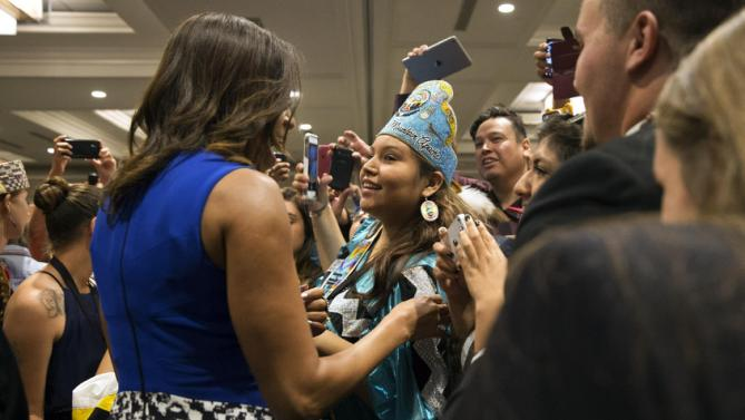 "Deandra Antonio, 17, of Whiteriver, Ariz., center, who is on the White Mountain Apache Nation and who serve on the White Mountain Apache youth council, is greeted by first lady Michelle Obama, left, after the first lady spoke at the first White House Tribal Youth Gathering, Thursday, July 9, 2015 in Washington.  Michelle Obama on Thursday told hundreds of Native American youth that they are all precious and sacred and that ""each of you was put on this earth for a reason.""  (AP Photo/Jacquelyn Martin)"