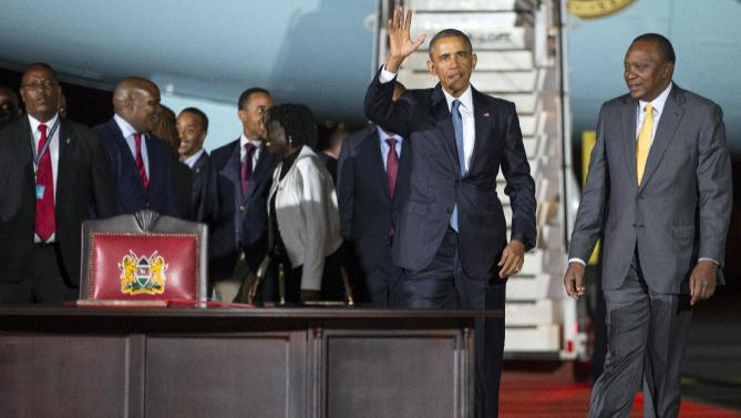 President Barack Obama waves as he walks with Kenyan President Uhuru Kenyatta to sign a guest book after arriving at Kenyatta International Airport, on Friday, July 24, 2015, in Nairobi, Kenya. Obama's link to Kenya, where he began his first visit as U.S. president, is a father he barely knew but whose influence can nonetheless be seen in his son's presidency. (AP Photo/Evan Vucci)
