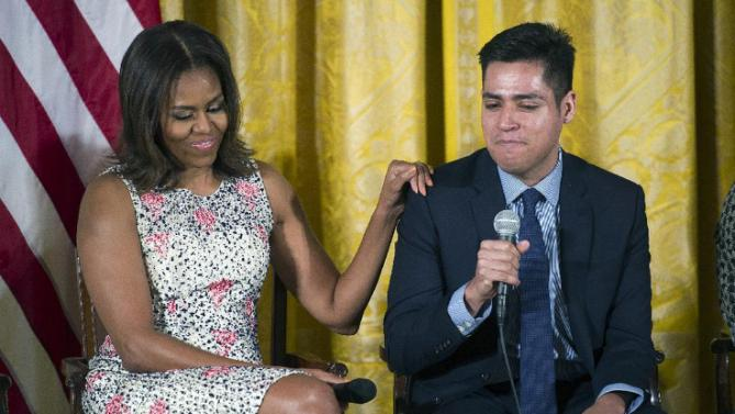 First lady Michelle Obama puts her hand on the shoulder of Brown University student Manuel Contraries, the son of two Mexican immigrants, after he spoke about his freshman year at school, during an East Room event to welcome more than 130 college-bound students from across the county to participate in the 2015 Beating the Odds Summit at the White House in Washington, Thursday, July 23, 2015. The summit is part of the first lady's Reach Higher initiative. (AP Photo/Cliff Owen)