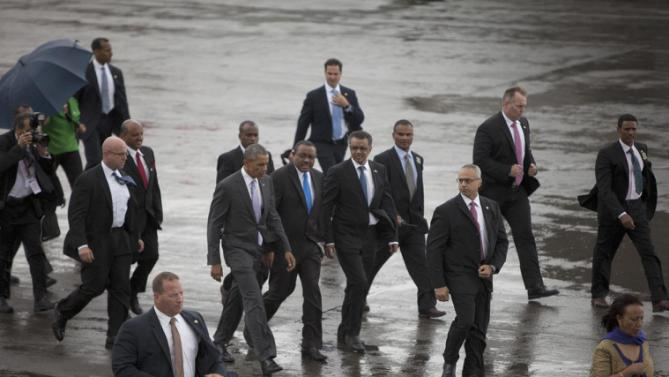 Surrounded by Secret Servicemen, US President Barack Obama, centre left, walks to Airforce One, with Ethiopian Prime Minister Hailemariam Desalegn,  as he departs Bole International Airport, Tuesday, July 28, 2015, in Addis Ababa, on the final day of his visit in Ethiopia. Closing a historic visit to Africa, President Barack Obama on Tuesday urged the continent's leaders to prioritize creating jobs and opportunity for the next generation of young people or risk sacrificing future economic potential to further instability and disorder. (AP Photo/Sayyid Azim)