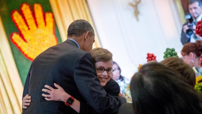 President Barack Obama gives a young guest a hug as he makes an unannounced appearance as first lady Michelle Obama hosts the 2015 winners of the Healthy Lunchtime Challenge for the Kids' State Dinner in the East Room at the White House, Friday, July 10, 2015, in Washington. (AP Photo/Andrew Harnik)