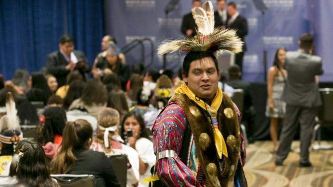 """Wearing traditional regalia Little Bear Johnson, 20, a member of the Kickapoo Nation, who is from Shawnee, Okla., dances to a pop song during a break in programming before the arrival of first lady Michelle Obama to speak to Native American youth at the first White House Tribal Youth Gathering, Thursday, July 9, 2015 in Washington. Obama told hundreds of Native American youths that they are all precious and sacred and that """"each of you was put on this earth for a reason."""" (AP Photo/Jacquelyn Martin)"""
