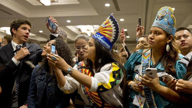 """Shasta Dazen, 21, center, of Whiteriver, Ariz., who is the 53rd Miss Indian Arizona, and Deandra Antonio, 17, right, both of the White Mountain Apache Nation and who serve on the White Mountain Apache youth council, vie for a glimpse of first lady Michelle Obama, after she spoke at the first White House Tribal Youth Gathering, Thursday, July 9, 2015 in Washington.  First lady Michelle Obama on Thursday told hundreds of Native American youth that they are all precious and sacred and that """"each of you was put on this earth for a reason."""" (AP Photo/Jacquelyn Martin)"""