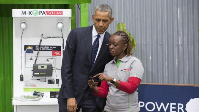 President Barack Obama looks at a mobile payment platform and solar exhibit during the Power Africa Innovation Fair, Saturday, July 25, 2015, in Nairobi. Obama's visit to Kenya is focused on trade and economic issues, as well as security and counterterrorism cooperation.  (AP Photo/Evan Vucci)