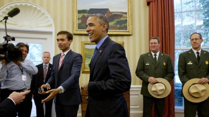 "White House press assistant Peter Velz, left, gestures to make a path for President Barack Obama, center, as the president walks away from his desk after designating three new national monuments; Berryessa Snow Mountain in California, Waco Mammoth in Texas, and the Basin and Range in Nevada, in the Oval Office of the White House Friday, July 10, 2015, in Washington. At right are Behind him from left are John ""Russ"" Whitlock, with the National Park Service, and Victor Knox, associate director of park planning, facilities and lands of the National Park Service. (AP Photo/Jacquelyn Martin)"