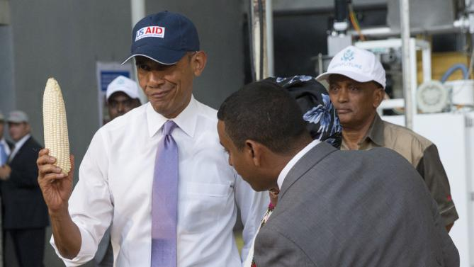 U.S. President Barack Obama holds up an ear of corn during a tour of Faffa Food, Tuesday, July 28, 2015, in Addis Ababa, Ethiopia. On the final day of his African trip, Obama is focusing on economic opportunities and African security. (AP Photo/Evan Vucci)
