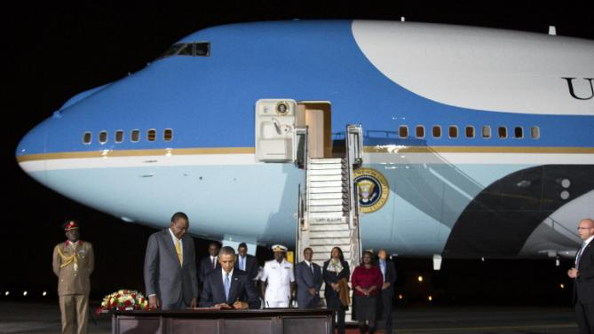 Kenyan President Uhuru Kenyatta, left, watches as President Barack Obama signs a guest book after arriving at Kenyatta International Airport, on Friday, July 24, 2015, in Nairobi, Kenya. Obama is traveling on a two-nation African tour where he becomes the the first sitting U.S. president to visit Kenya and Ethiopia. (AP Photo/Evan Vucci)