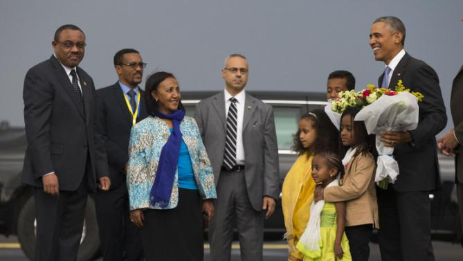 Ethiopian Prime Minister Hailemariam Desalegn, left, looks on as President Barack Obama is given a bouquet of flowers as he arrives at Addis Ababa Bole International Airport, on Sunday, July 26, 2015, in Addis Ababa. Obama is the first sitting U.S. president to visit Ethiopia. (AP Photo/Evan Vucci)
