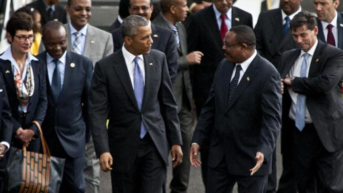 U.S President Barack Obama, left, walks with Ethiopian prime minister Hailemariam Desalegn, right, after his arrival at Bole International Airport, Addis Ababa, Ethiopia, Sunday, July 26, 2015.  Obama is traveling on a two-nation African tour where he will become the the first sitting U.S. president to visit Kenya and Ethiopia. (AP Photo/Sayyid Azim)