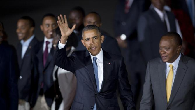 U.S. President Barack Obama waves after being greeted by Kenya's President Uhuru Kenyatta, right, on his arrival at the Jomo Kenyatta International Airport in Nairobi, Kenya Friday, July 24, 2015. Obama began his first visit to Kenya as U.S. president Friday. (AP Photo/Ben Curtis)
