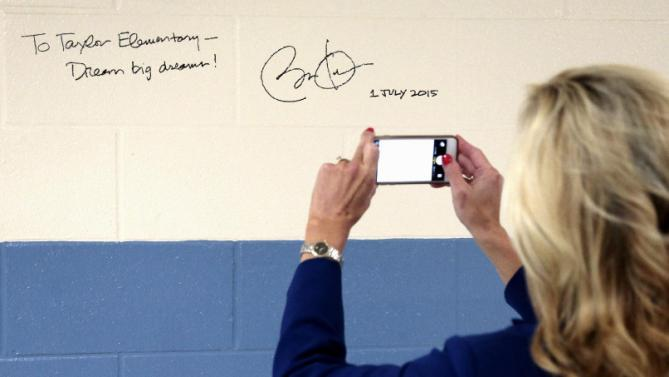 A woman photographs an autograph left by President Barack Obama on a wall at Taylor Stratton Elementary School in Nashville, Tenn., Wednesday, July 1, 2015, after Obama spoke at the school about the Affordable Care Act. (AP Photo/Mark Humphrey)