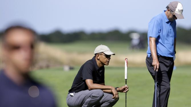 President Barack Obama, center, squats down near a green as Glenn Hutchins, right, stands nearby while golfing Monday, Aug. 10, 2015, at Vineyard Golf Club, in Edgartown, Mass., on the island of Martha's Vineyard. The president is staying on Martha's Vineyard with first lady Michelle Obama and daughter Sasha for a 17-day island retreat. A member of law enforcement, left, watches. (AP Photo/Steven Senne)