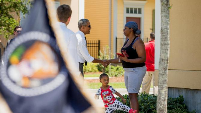 A presidential flag on a presidential limo can be seen as President Barack Obama, greets a resident in the the Tremé neighborhood in New Orleans, Thursday, Aug. 27, 2015, for the 10th anniversary since the devastation of Hurricane Katrina. Tremé is one of the oldest black neighborhoods in America, which borders the French Quarter just north of Downtown. (AP Photo/Andrew Harnik)