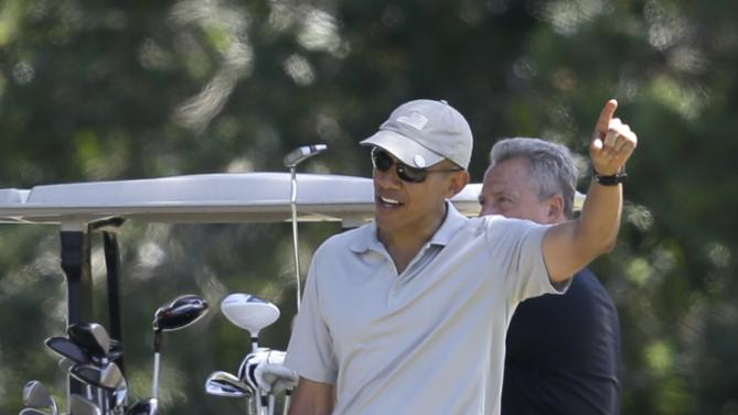 President Barack Obama, front, gestures while talking as golf partner Robert Wolf, behind right, looks on while golfing Saturday, Aug. 8, 2015, at Farm Neck Golf Club, in Oak Bluffs, Mass., on the island of Martha's Vineyard. Obama is spending his first full day of vacation on the island playing golf. (AP Photo/Steven Senne)