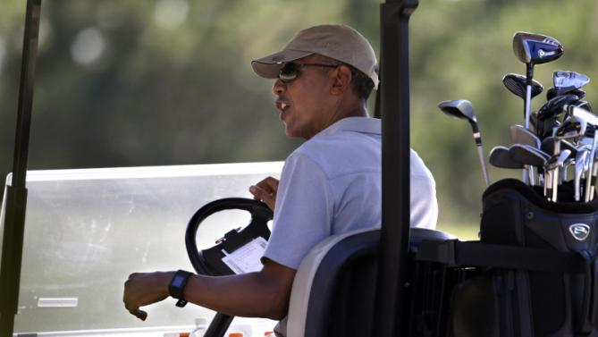 President Barack Obama drives a golf cart while golfing Wednesday, Aug. 12, 2015, at Farm Neck Golf Club, in Oak Bluffs, Mass., on the island of Martha's Vineyard. The president, first lady Michelle Obama, and daughter Sasha are vacationing on the island. (AP Photo/Steven Senne)