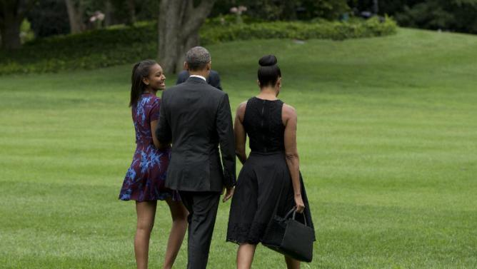 President Barack Obama, center, first lady Michelle Obama, right, and their daughter Sasha walk across the South Lawn of the White House to board Marine One in Washington, Friday, Aug. 7, 2015, en route to Andrews Air Force Base, Md., and onto Martha's Vineyard, Mass., for a family vacation. (AP Photo/Carolyn Kaster)