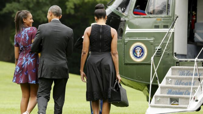 Sasha Obama (C) smiles while walking with her parents U.S. President Barack Obama and first lady Michelle Obama as they depart for their annual summer vacation to Martha's Vineyard from the South Lawn of the White House in Washington August 7, 2015. REUTERS/Jonathan Ernst